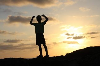 boy standing with his arms up in victory