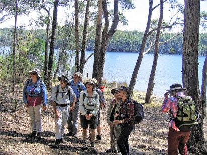 Walkers pause on the shores of the lake.