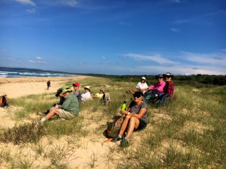 The group take a break in the dunes enjoying the sunshine.