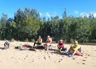 Sharon, Bob, Len, Lyn and leader Ian lunching on a sandy beach.