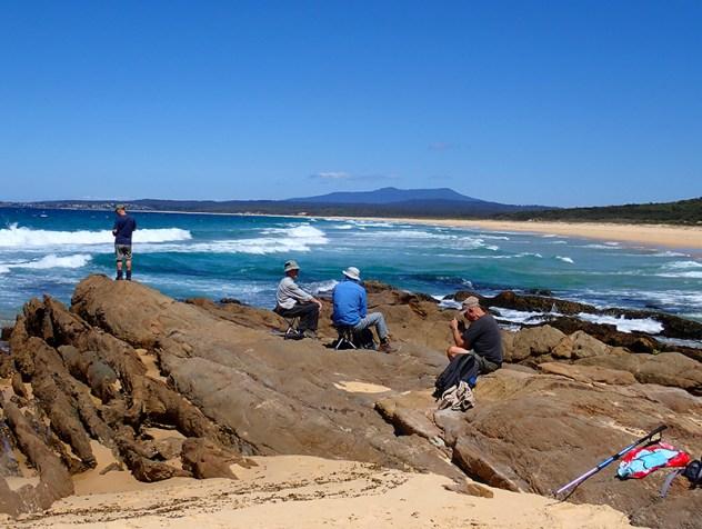 4 men, sand, rocks, sea and mountain.