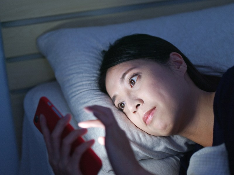 Woman watch on cellphone and lying on bed at night