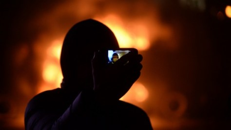 Masked_protester_taking_jis_self_portrait_against_background_of_barricades_on_fire._Dynamivska_str._Euromaidan_Protests._Events_of_Jan_19__2014