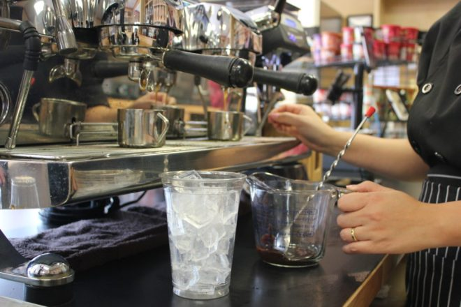 barista making an iced coffee