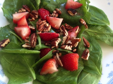 strawberries and pecans on spinach