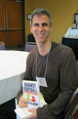 author holding copy of Against Football