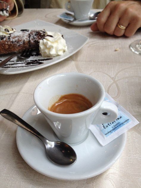 espresso in cup with a cannolo in background