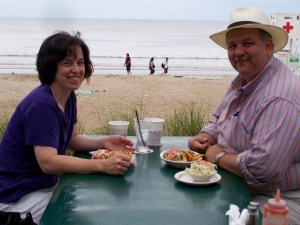 Me and my husband at a table on the beach
