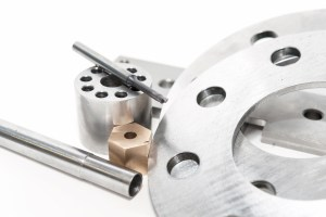 Metal flanges and brass nuts. Metalworking CNC milling/lathe industry. Closeup.