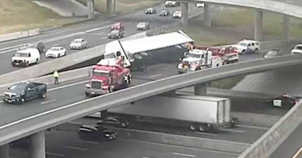Truck tips on turn and is left teetering over Highway 401