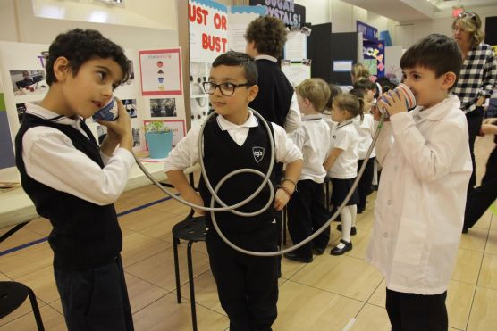Can you hear me now? Grade One boys discovering sound travel.