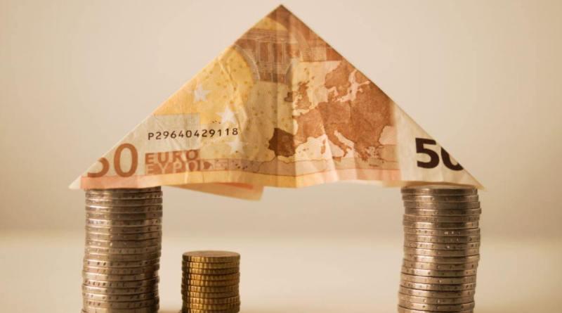 maison avec billet et pièces de monnaie