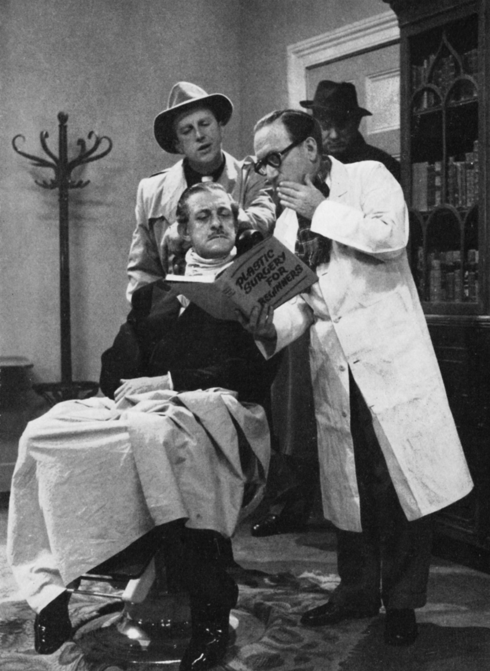 "Leslie Mitchell in a doctor's chair with Arthur Askey looming over him with a book entitled ""PLASTIC SURGERY FOR BEGINNERS"""