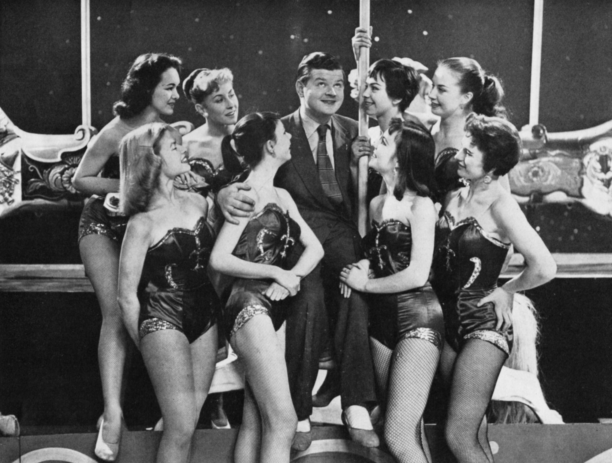Benny Hill sits on the edge of a carousel whilse surrounded by 8 girls in skimpy costumes