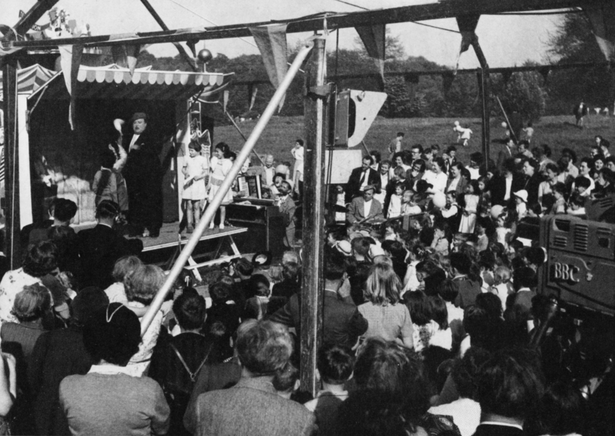 A crowd of children watch a magician on an outdoor stage