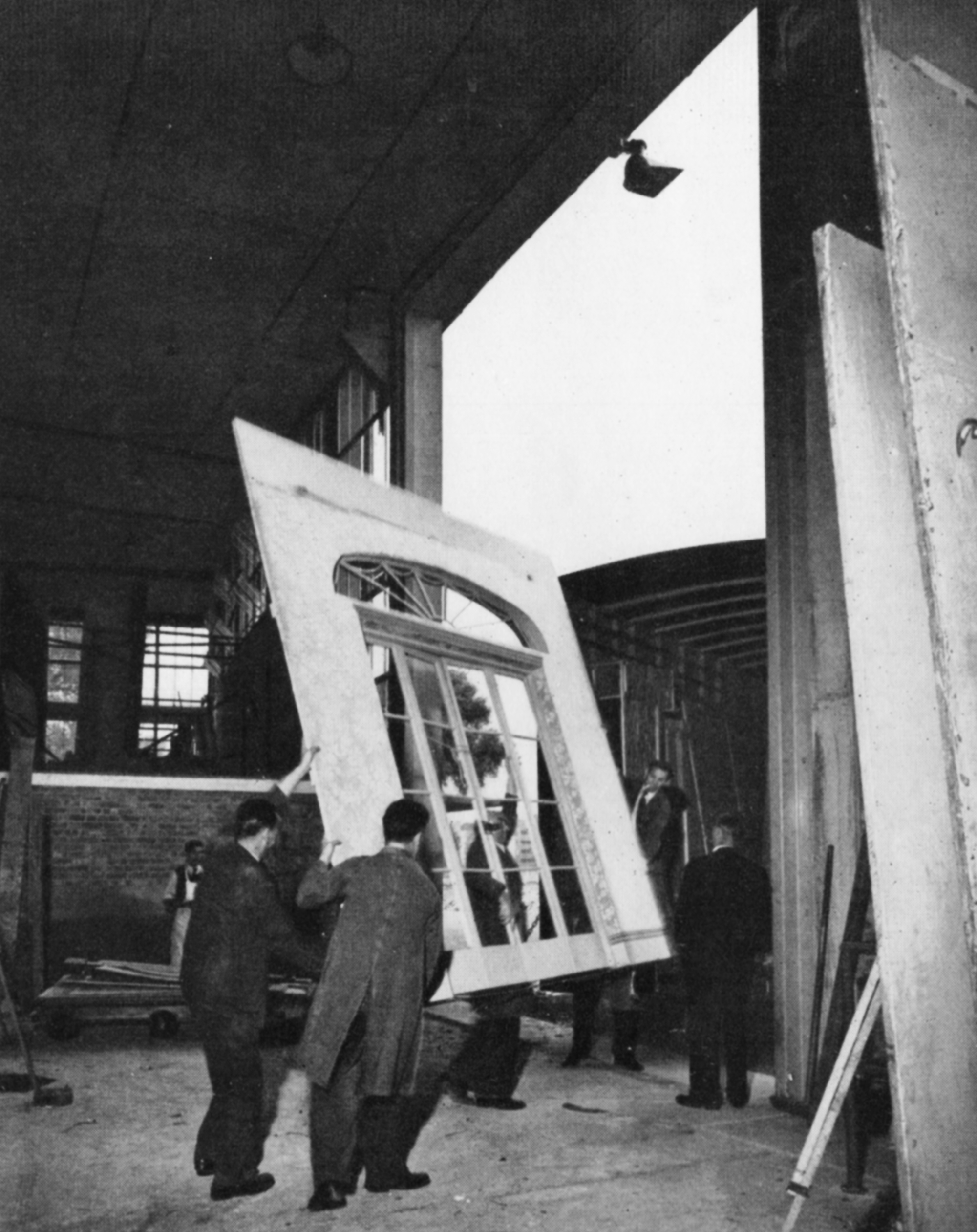 Men manoeuvre a set of French doors through the huge door of the warehouse and on to a removals van.