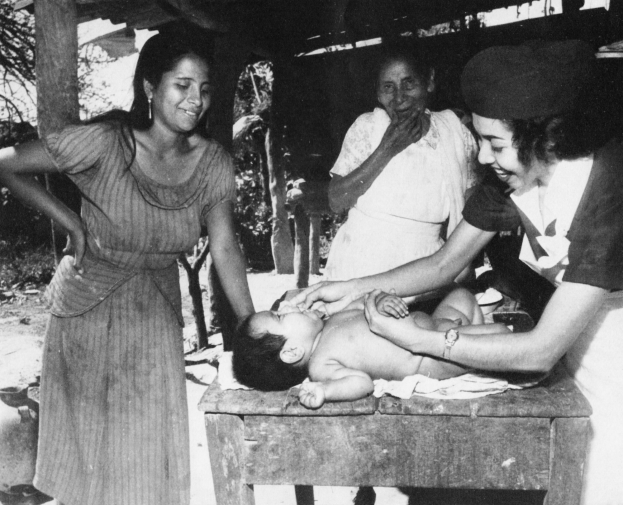 A child is examined by a nurse as his mother stands over him