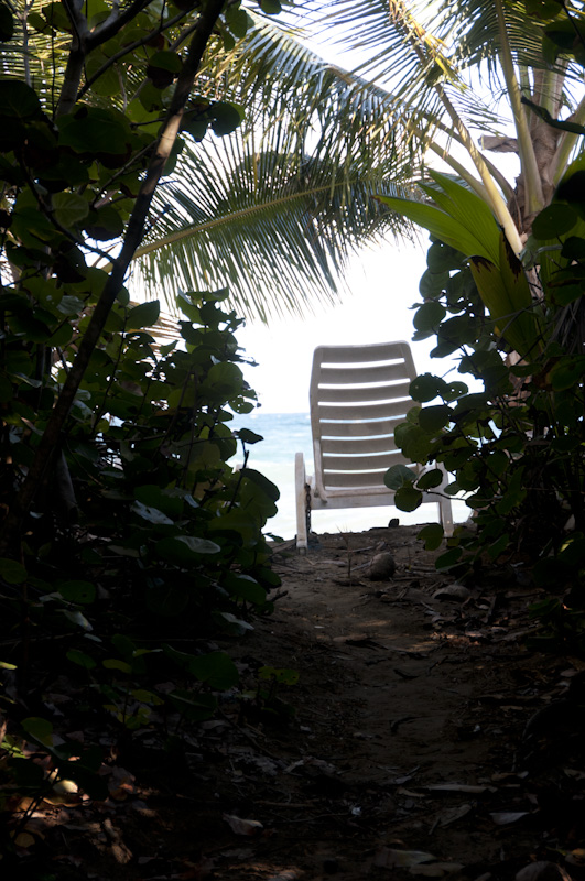 A deck chair on the villa beach as you come from the trees.