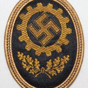 P003. WWII GERMAN DAF VISOR CAP BADGE