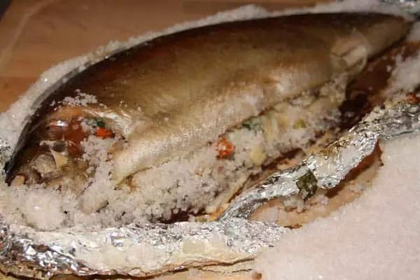 Vorsichtig den Salzmantel von der Lachsforelle entfernen