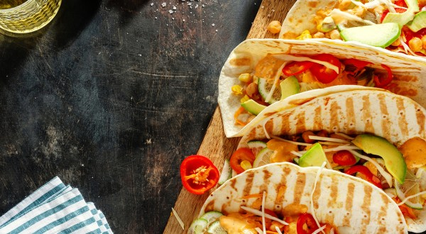 Appetizing, fresh, homemade vegan tacos with cut up vegetables in tortillas and served on wooden board