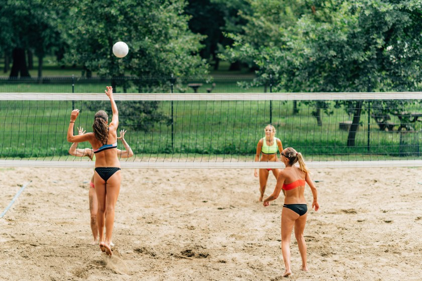 Women in swimsuits playing volleyball outdoors and hitting the ball over the net