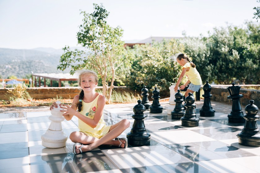 Young children playing a game of outdoor giant chess