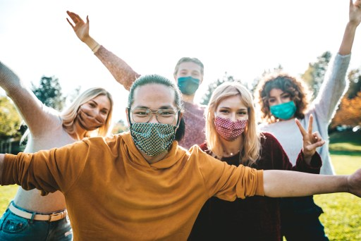 Group of friends outside wearing masks over their mouths and noses