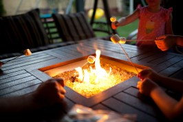Young kids roasting marshmallows in their backyard around a firepit