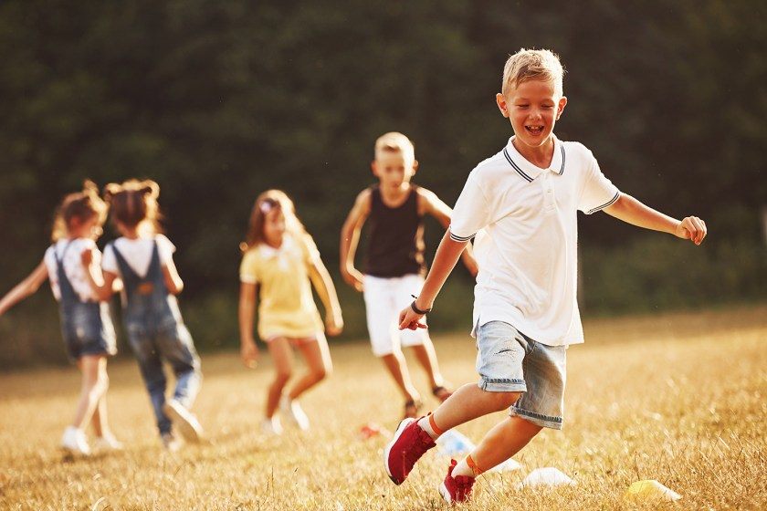Kids laughing and running in the grass of a backyard on a sunny day