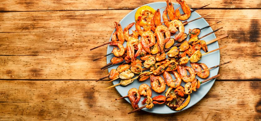 Grilled seafood kebabs on a plate on a table