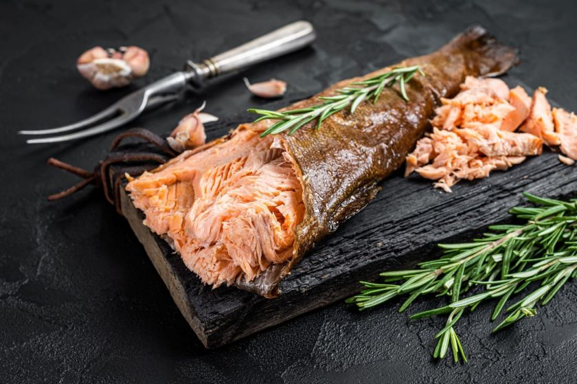 Fish on a black board that has been smoked and is cut open with some pieces cooked next to it and a fork and some garnish.