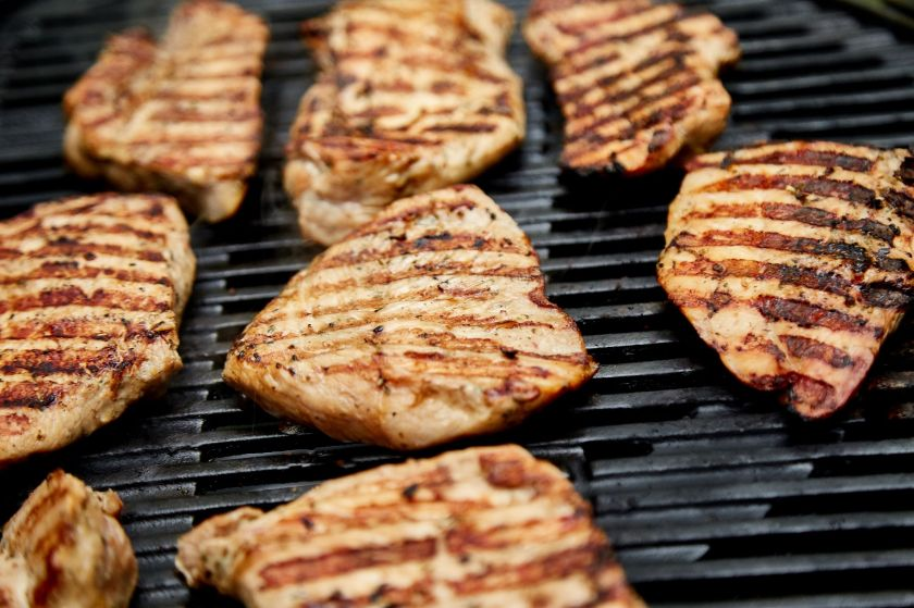 Cuts of grilled turkey steak on a grill with grill marks on the side of the cut facing up.