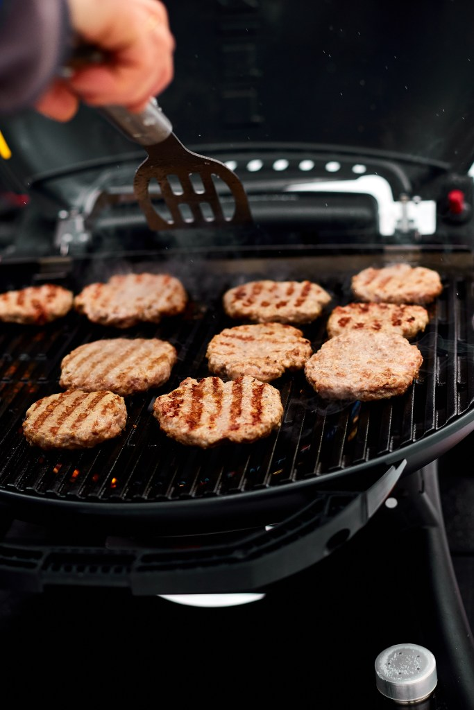 Close up of portable grill outside with burgers that are almost done getting cooked.