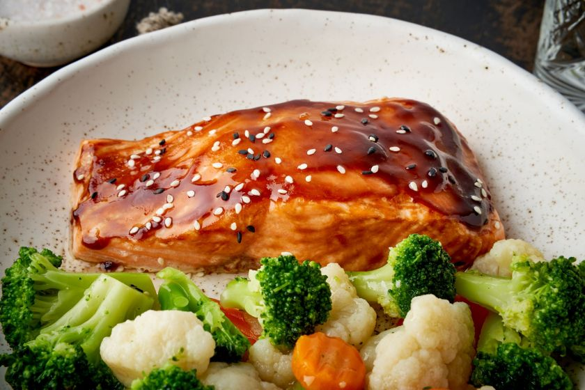 Salmon with a teriyaki marinade that is tasty and has sesame seeds in it and is plated next to fresh veggies.