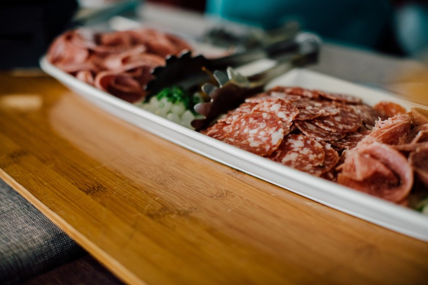 A charcuterie platter displaying different slices of meats with tongs in the middle to grab some to eat.