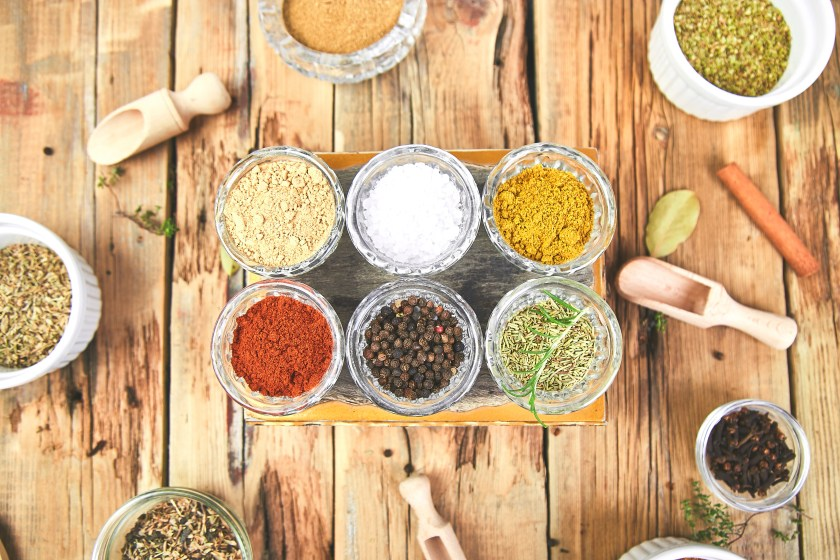 Different spices and herbs in jars on a wooden table surrounded by other herbs and scoops.