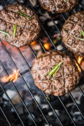 Beef Burgers On Grill With Flames From Charcoal, Overhead View