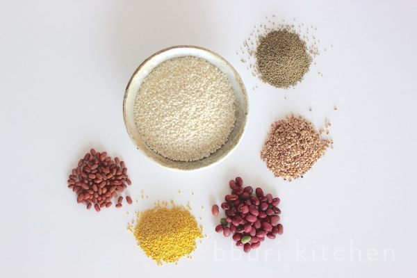 Center: chap-ssal (glutinous rice). From L to R: pat (read bean), gijang-ssal (proso millet), gangnang-kong (kidney bean), susu (sorghum), chajo (glutinous millet)