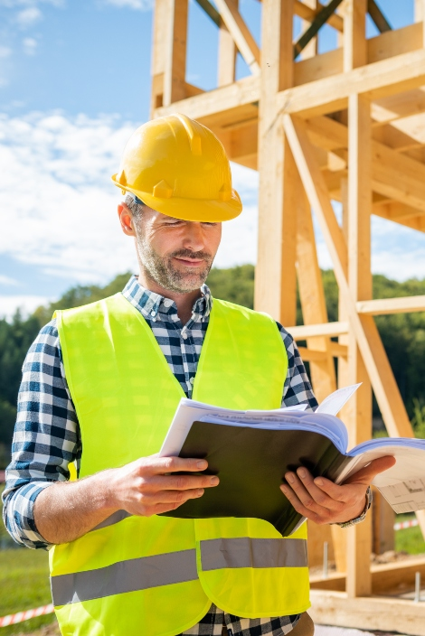 engineer-with-hardhat-and-blueprints-on-building-s-W79PR8B-1.jpg