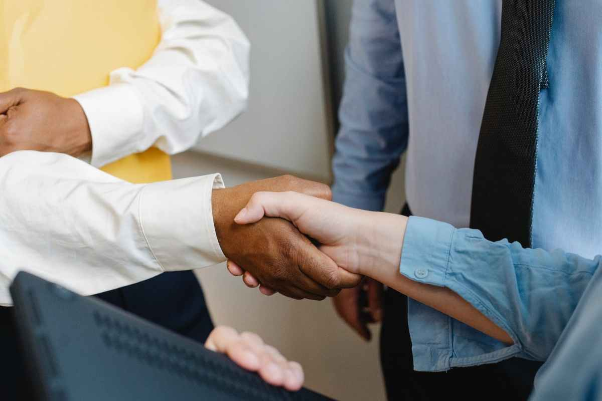 multiracial colleagues shaking hands at work