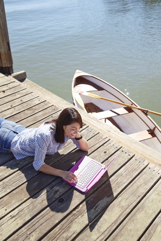 """Woman works on a boat dock from an HP Stream 13"""" notebook."""