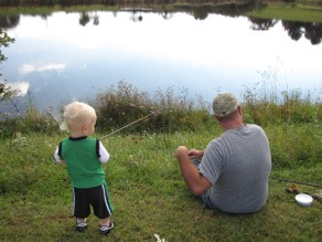 Son and father fishing on the bank
