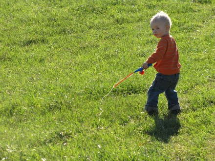 My son fishing in the field on his way to the woods.