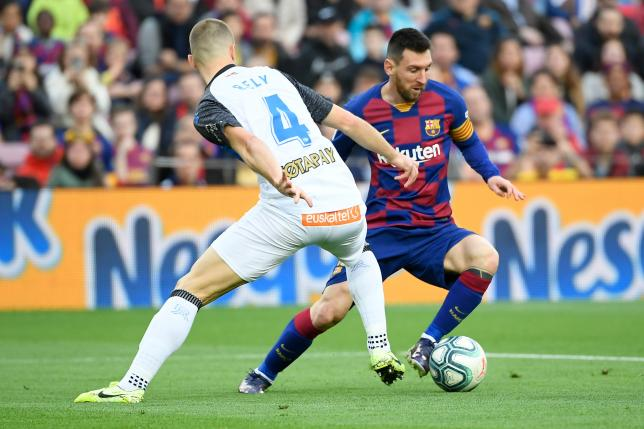 Alaves` Brazilian defender Rodrigo Ely (R) challenges Barcelona`s Argentine forward Lionel Messi during the Spanish league football match FC Barcelona against Deportivo Alaves at the Camp Nou stadium in Barcelona on 21 December 2019. Photo: AFP