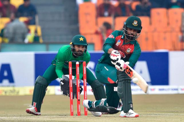 Bangladesh`s batsman Liton Das (R) plays a shot as Pakistani wicketkeeper Mohammad Rizwan looks on during the second T20 international cricket match of a three-match series between Pakistan and Bangladesh, at Gaddafi Cricket Stadium in Lahore on 25 January, 2020. Photo:AFP
