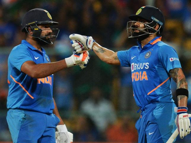 India`s Virat Kohli (R) and Rohit Sharma greet each other during the third and last one day international (ODI) cricket match of a three-match series between India and Australia at the M. Chinnaswamy Stadium in Bangalore on 19 January 2020. Photo: AFP