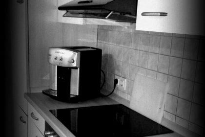 Küche mit Backofen, Kühlschrank und Kaffeevollautomat