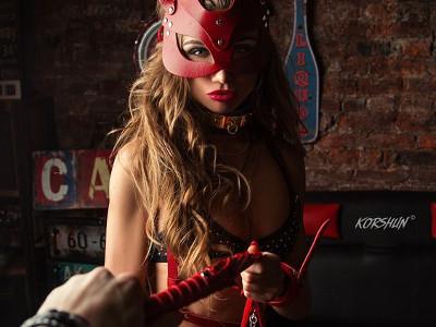 Femme au masque de cuir rouge fouet rouge et noir