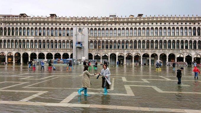 ベネチアのサンマルコ広場で冠水している広場で記念撮影する観光客